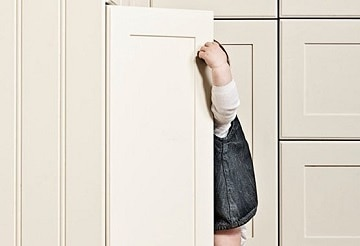 Toddler opening kitchen cupboard